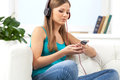 Happy girl enjoying music on mp player closeup of brunette sitting sofa at home Stock Images