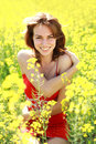 Happy girl enjoying the nature on a sunny day in the flowering yellow field Royalty Free Stock Photos