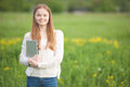 Happy Girl European appearance standing on the grass with a laptop on green nature background Royalty Free Stock Photo