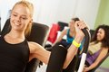 Happy girl exercising at the gym doing keep fit exercises on weight machine Stock Photo
