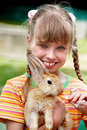 Happy girl feed rabbit with carrot. Royalty Free Stock Images