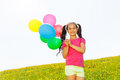 Happy girl with flying balloons in the air during sunny day Stock Image