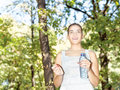 Happy girl in forest holding bottle of water Royalty Free Stock Image