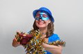 Happy girl with a gift in blue dress hat and mask meshure and Stock Photo
