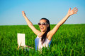 Happy girl in a green field with outstretched arms laptop Royalty Free Stock Photography