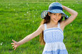 Happy girl on the green meadow in hat Stock Image