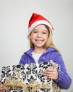 Happy girl holding christmas gift portrait of in santa hat at home Stock Image