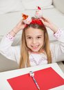 Happy girl holding santa headband portrait of with pencil and cardpaper at home Royalty Free Stock Photography