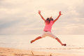 Happy girl jumping on the beach at sunset young for joy Royalty Free Stock Photos