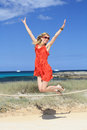 Happy girl jumping and laughing on the beach in a red dress sunglasses Stock Image