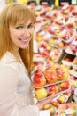 Happy girl keeps packed apples in store Royalty Free Stock Photo