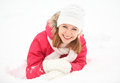 Happy girl laughs while lying on the snow in winter outdoors Royalty Free Stock Photo