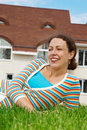 Happy girl on lawn in front of new home. Stock Photography