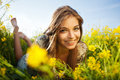 Happy girl lies among yellow wildflowers cute Stock Photography
