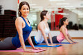 Happy girl loving her yoga class beautiful young women trying the cobra pose and smiling during Royalty Free Stock Image