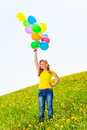 Happy girl with many flying balloons in the air summer meadow yellow dandelions Stock Images