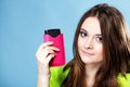 Happy girl with mobile phone in pink cover young woman smartphone studio shot blue background Royalty Free Stock Photo