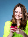 Happy girl with mobile phone reads message smiling blue background Royalty Free Stock Photo
