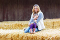Happy girl and mother having fun with hay on a farm Royalty Free Stock Photo