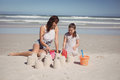Happy girl with mother making sand castle at beach Royalty Free Stock Photo