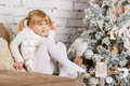 Happy girl near christmas tree pretty sits on a sofa in the room Stock Photography