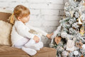 Happy girl near christmas tree pretty sits on a sofa in the room Stock Images