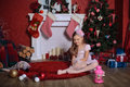 Happy girl near christmas tree in rose dress and lace gloves sitting on a carpet Stock Photography