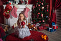 Happy girl near christmas tree sitting on a carpet and holding red glitter ball in hands Royalty Free Stock Photos