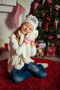 Happy girl near christmas tree sitting on a carpet and holding snowballs in hands Royalty Free Stock Images