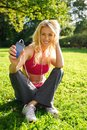 Happy girl outdoors young smiling blond athletic sitting on grass in a park with smartphone and earphones Royalty Free Stock Images