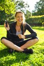 Happy girl outdoors young smiling brunette athletic sitting on grass in a park with smartphone and earphones Royalty Free Stock Image