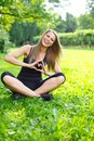 Happy girl outdoors young sporty showing heart sign with her hands on a meadow in a park Royalty Free Stock Photos
