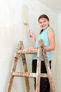 Happy girl paints wall with roller Stock Photography