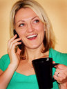 Happy girl on phone holding cup Stock Photo