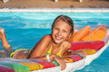 Happy girl playing in blue water of swimming pool. Royalty Free Stock Photo