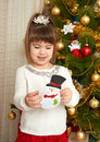 Happy girl portrait in christmas decoration, playing with snowman toy, winter holiday concept, decorated fir tree and gifts Royalty Free Stock Photo