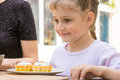 Happy girl is preparing to eat cupcakes Royalty Free Stock Photo