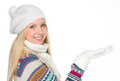 Happy girl presenting something on empty palm in winter clothes Stock Images