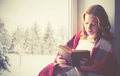 Happy girl reading book by the window in winter Royalty Free Stock Photo