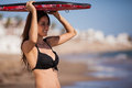 Happy girl ready to surf beautiful young woman holding a body board on top of her head cover from the sun and smiling Royalty Free Stock Image