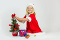 Happy girl in a red christmas costume sweet decorates the tree and smiling Royalty Free Stock Photo