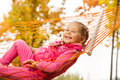 Happy girl relaxing and laying on net of hammock Royalty Free Stock Photo