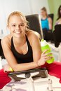 Happy girl resting at the gym fit drinking refreshment smiling Royalty Free Stock Photos