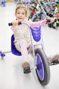 Happy girl rides tricycle and looks at camera Royalty Free Stock Photography