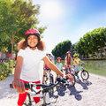 Happy girl riding bike with friends on river bank Royalty Free Stock Photo