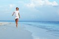 Happy girl run along the ocean coast Royalty Free Stock Image