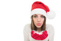 Happy girl with santa beanie hat blowing snow young and beautiful caucasian woman looking at camera holding isolated on white Royalty Free Stock Image
