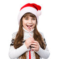 Happy girl in santa hat with christmas candy cane on white Stock Photography