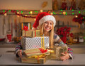Happy girl in santa hat with stack of christmas present boxes Royalty Free Stock Photo