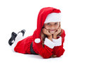 Happy girl in santa outfit smiling laying on the floor isolated Royalty Free Stock Photos